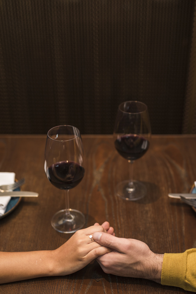man-woman-holding-hands-table-with-glasses-wine-restaurant_23-2148016832
